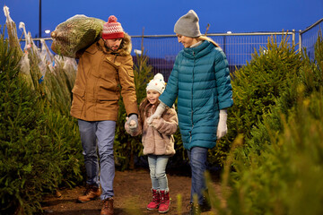 family, winter holidays and people concept - happy mother, father and little daughter buying christmas tree at street market in evening