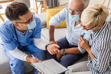 Male nurse talking to seniors patients with mask while being in a home visit.