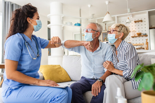 Female nurse greeting with seniors patients with mask while being in a home visit.