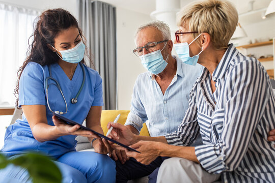 Female nurse talking to seniors patients with mask while being in a home visit, senior couple signs an insurance policy.