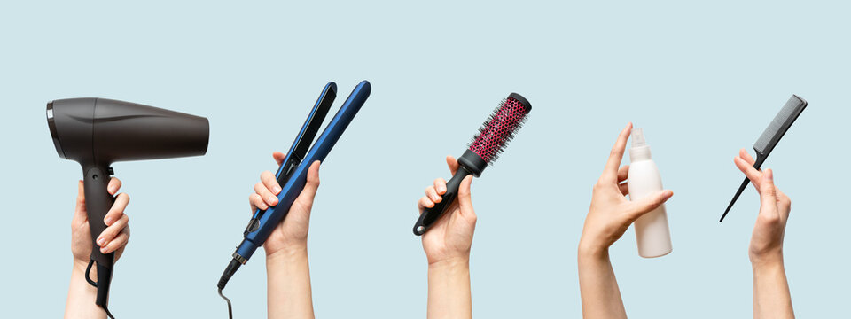 Woman hands holding hairdryer, straightener, hairbrush, tail comb and hair care essence in bottle isolated on blue background, horizontal banner format
