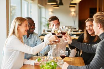 Freunde stoßen an mit Wein und feiern