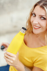 Young woman holding yellow reusable bottle