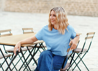 Young women wearing t-shirt and jeans sits in a street cafe