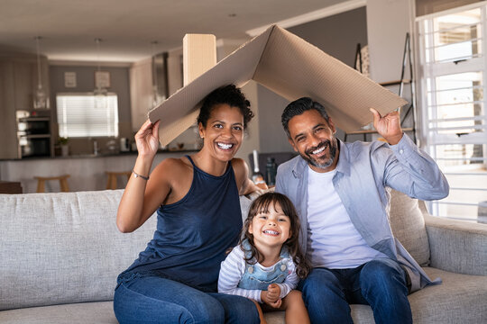 Happy multiethnic family with child holding cardboard roof