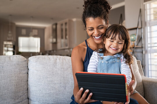 African smiling mother and happy daughter using digital tablet