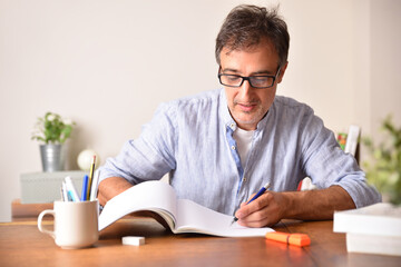 Smiling adult man tudying on wooden table underlining in book.