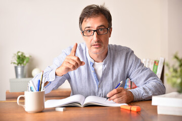 Serious tutor with raised finger writing in a book