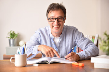 Smiling adult man tudying on wooden table writing in book