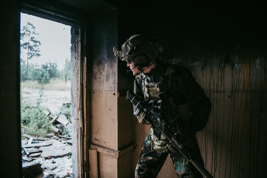 Soldier in full US MARSOC armed with assault rifle run through the abandoned building. Military clash.