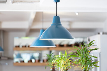 blue metal lamp hanging from white ceiling in living room.  blue steel lamp decoration.