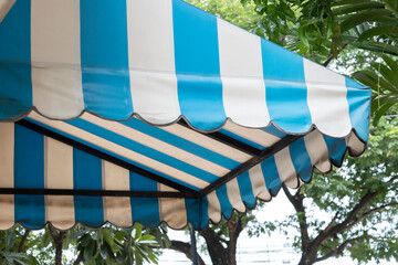 blue and white striped awning of shop with tree background.