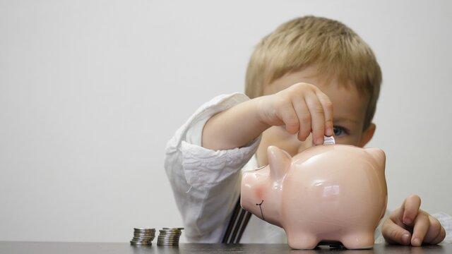 Economical child put money in piggy bank, treasure saving