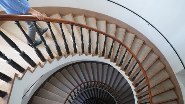 Man going down the interior spiral stairs of luxury modern building