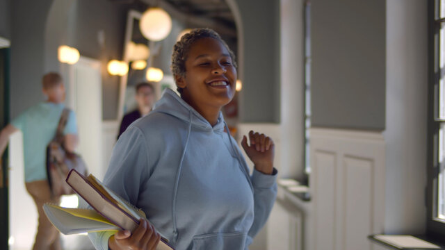 Happy university female student holding books and dancing walking along corridor