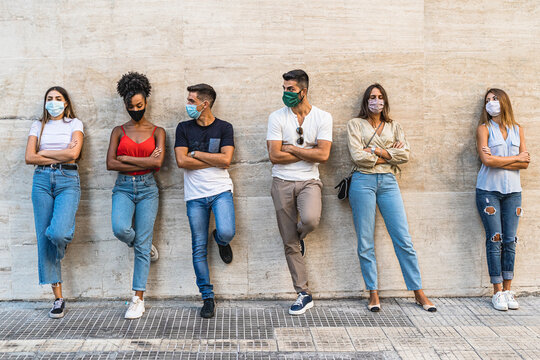 multiethnic group of teens with their backs leaning on wall and folded arms wearing masks to protect themselves from the coronavirus together