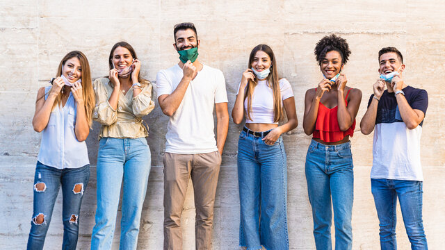 Multi-ethnic group of young friends smiling with coronavirus protective face mask down. People returned to meet together in a new normal life during Covid-19 virus after the lockdown.