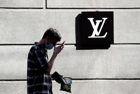 Man wearing a protective face mask walks past a logo of Louis Vuitton company outside a Louis Vuitton store in central Kyiv