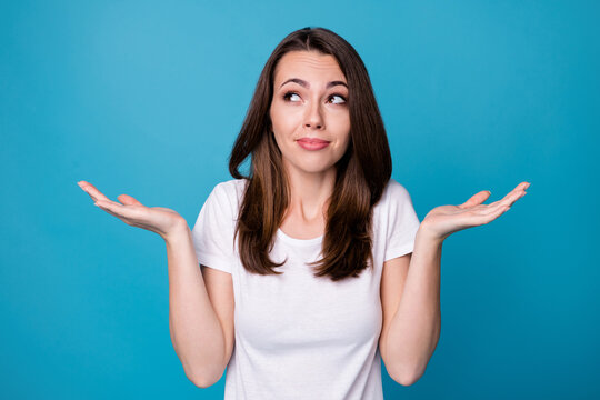 Sorry I don't care. Photo of attractive funny lady hold arms hands up shrug shoulders not feel guilty bad person wear casual white t-shirt isolated blue color background
