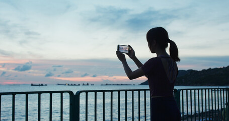 Woman use of mobile photo take photo at sunset time beside the sea