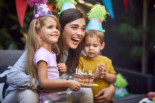 beautiful brunette laughing between little girl and boy with extinguished candles on birthday cake