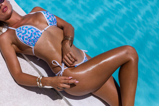 Beautiful tanned fit caucasian woman bronze shiny skin in bikini with coconut oil by blue swimming pool, sunny day.