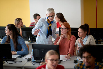 Female professor inspecting the work of students at an informatics lecture