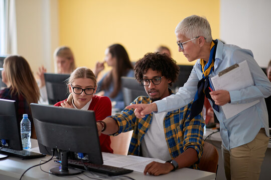 Female professor checking students work at an informatics lecture