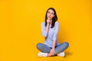 Portrait of her she nice attractive pretty smart clever curious cheery girl sitting lotus position overthinking making decision isolated bright vivid shine vibrant yellow color background