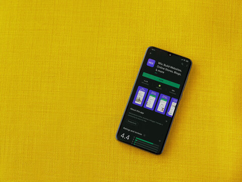 Lod, Israel - July 8, 2020: Wix app play store page on the display of a black mobile smartphone on a yellow fabric background. Top view flat lay with copy space.