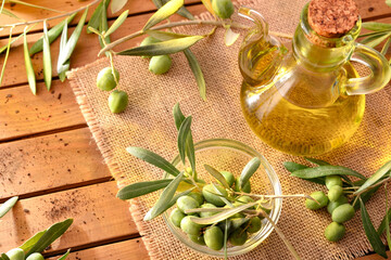 Olive oil on table with branches and olives elevated view