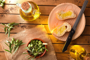Slices of bread with oil on wooden table in countryside