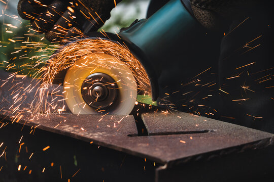 grinding cutting metal sheet with angle grinder machine and sparks, Close up