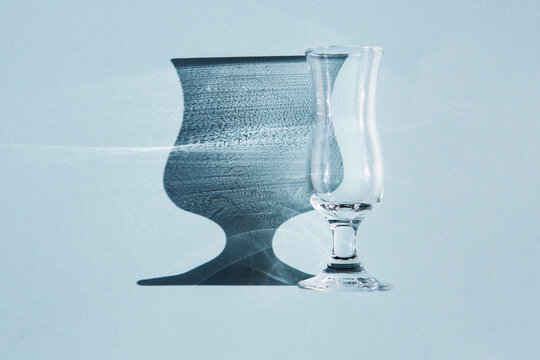 A small transparent and glass wine glass or glass lies on a blue background. Beautiful shade from sunlight.
