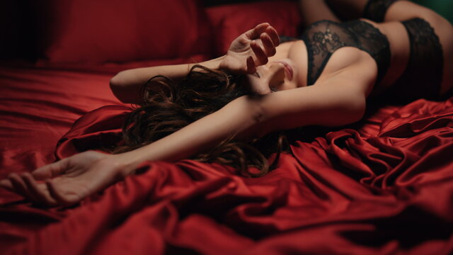 Sexy lingerie woman lying on red silk sheets. Lace lingerie girl curving on bed.