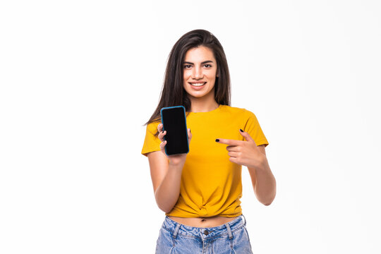 Young pretty smiling woman pointing with finger on phone screen, over white background