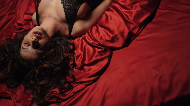 Sexy girl looking camera on red silk bed. Charming woman relaxing satin sheets.