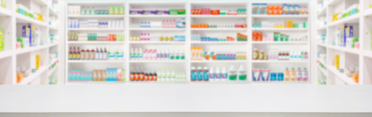 Empty wood counter top with pharmacy drugstore shelves blur pharmaceutical medicine product...