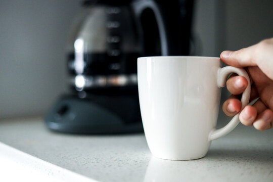 Holding white coffee cup in front of coffee maker