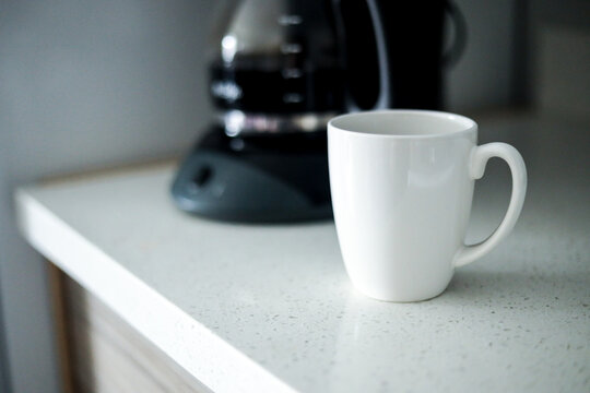 White coffee cup in front of coffee maker