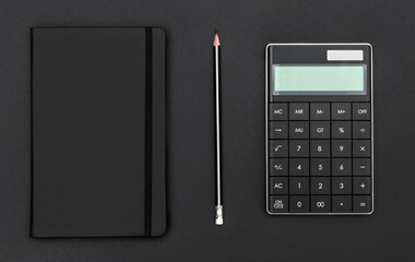 Notepad, pencil and calculator on black background. Top view. Business concept.