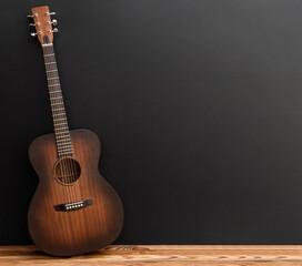 Wooden classical acoustic guitar stands near blackwall.