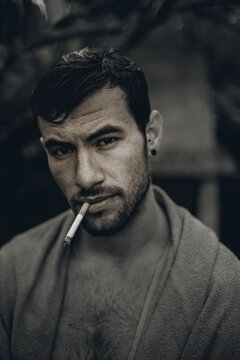 Guy with a cigarette in his mouth. Black and white photo.