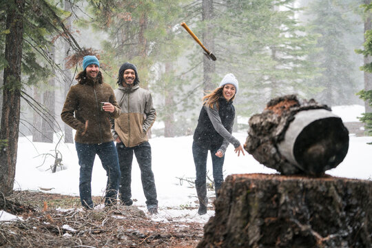 Young woman throws axe at a target in the snowy woods while her friends watch