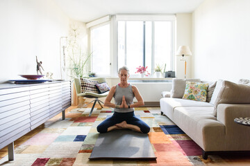 Senior woman in sitting meditation pose in home on yoga mat