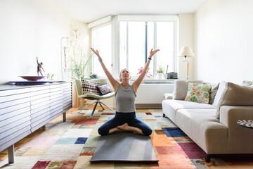 Senior woman lifting hands in yoga meditation in apartment