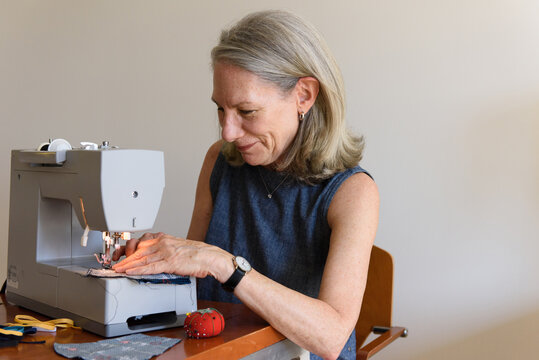 Senior woman smiling while sewing masks at home