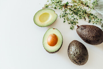 Top view of hass avocado and thyme on white background, healthy food