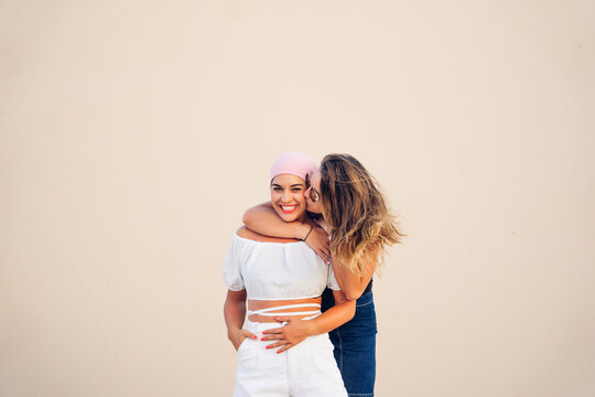 Young woman with pink headscarf fighting cancer together with her friend.