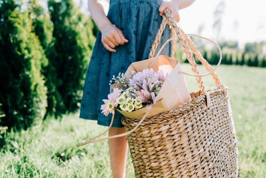 young girl holding a basket with a beautiful bunch of flowers in